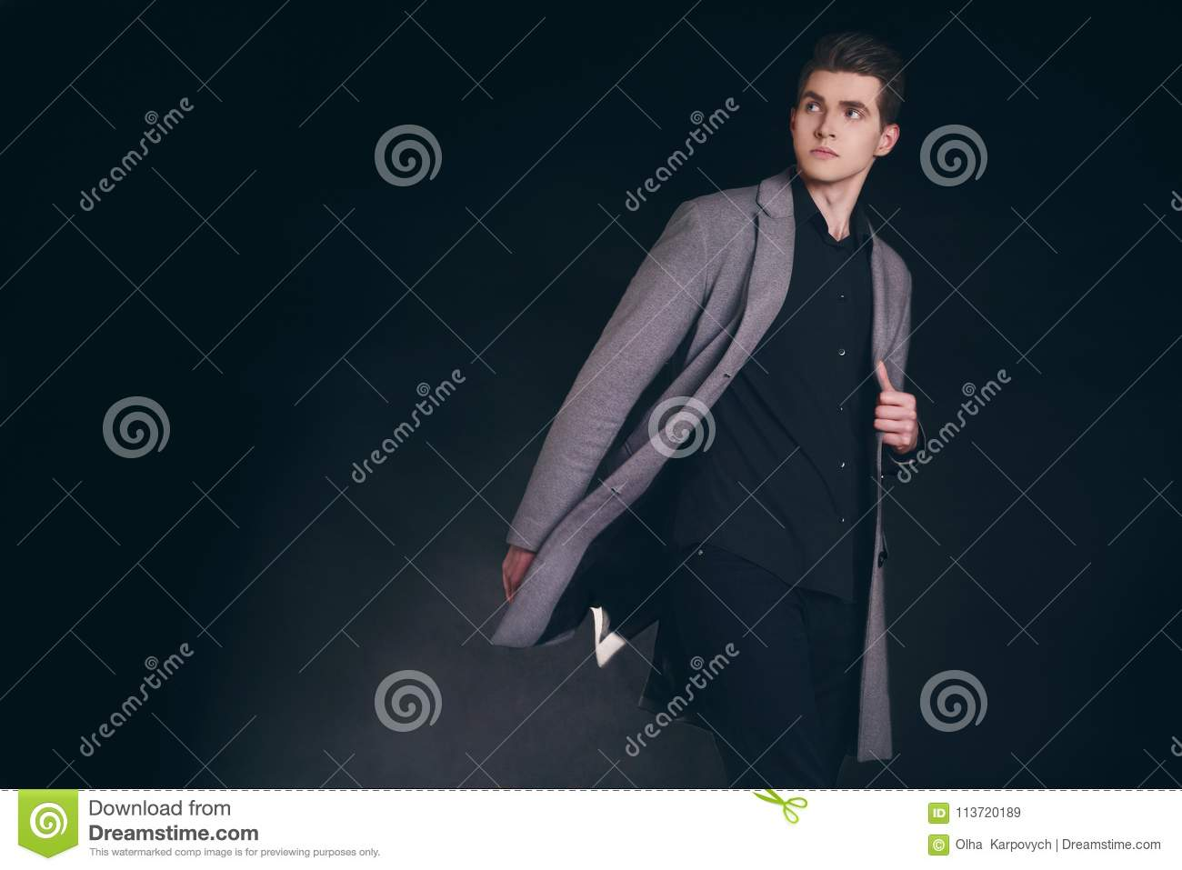 Young handsome man in coat. Portrait of fashionable well dressed man posing in grey stylish coat. Confident and focused boy