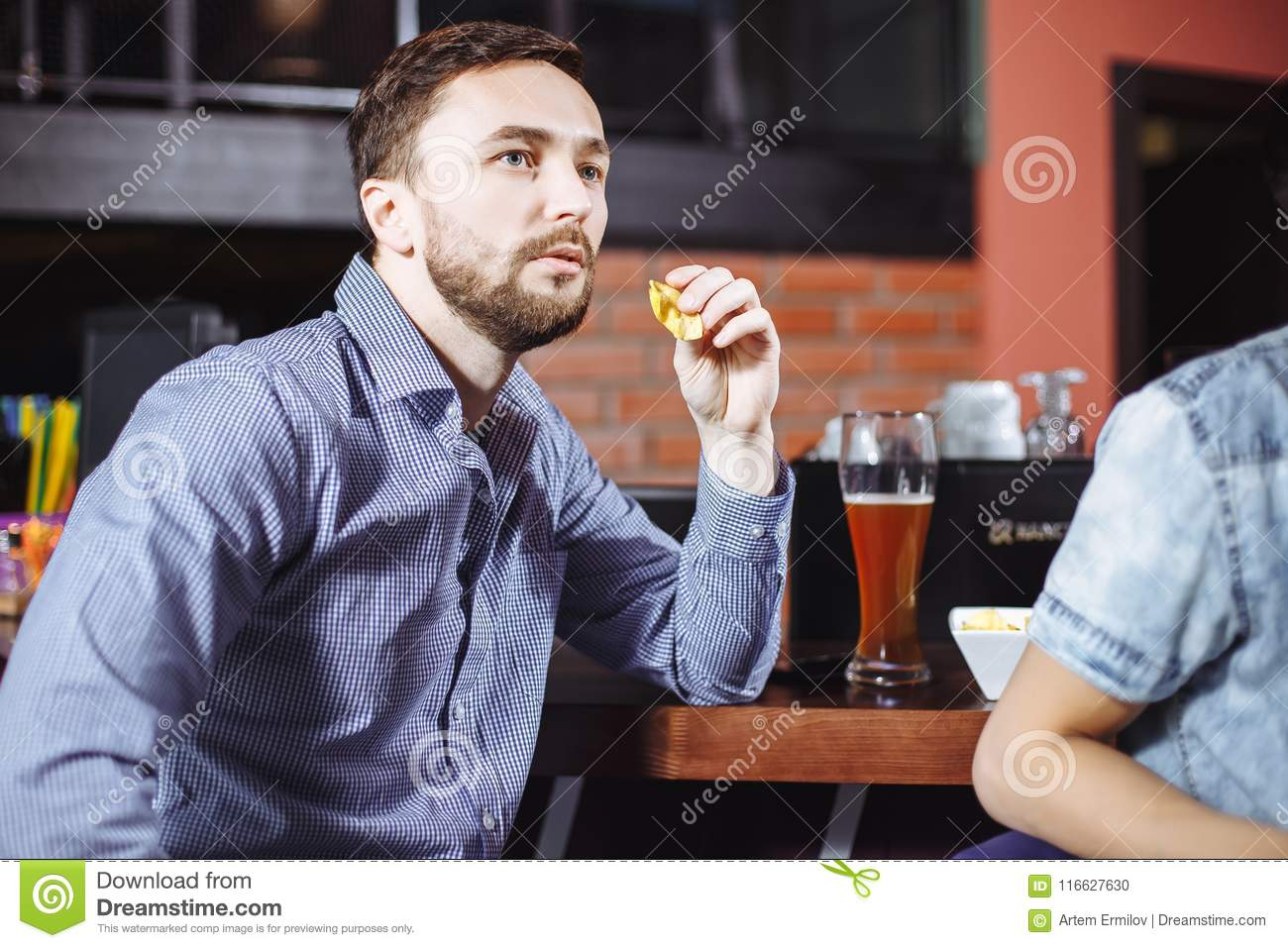 Young handsome man drinking beer and watching the game on TV in the bar