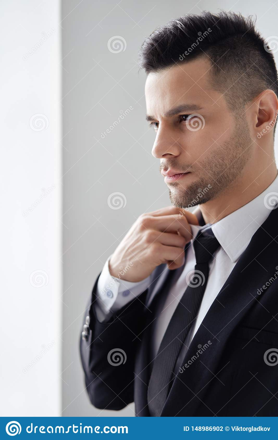 Young handsome man in elegant suit adjust his necktie