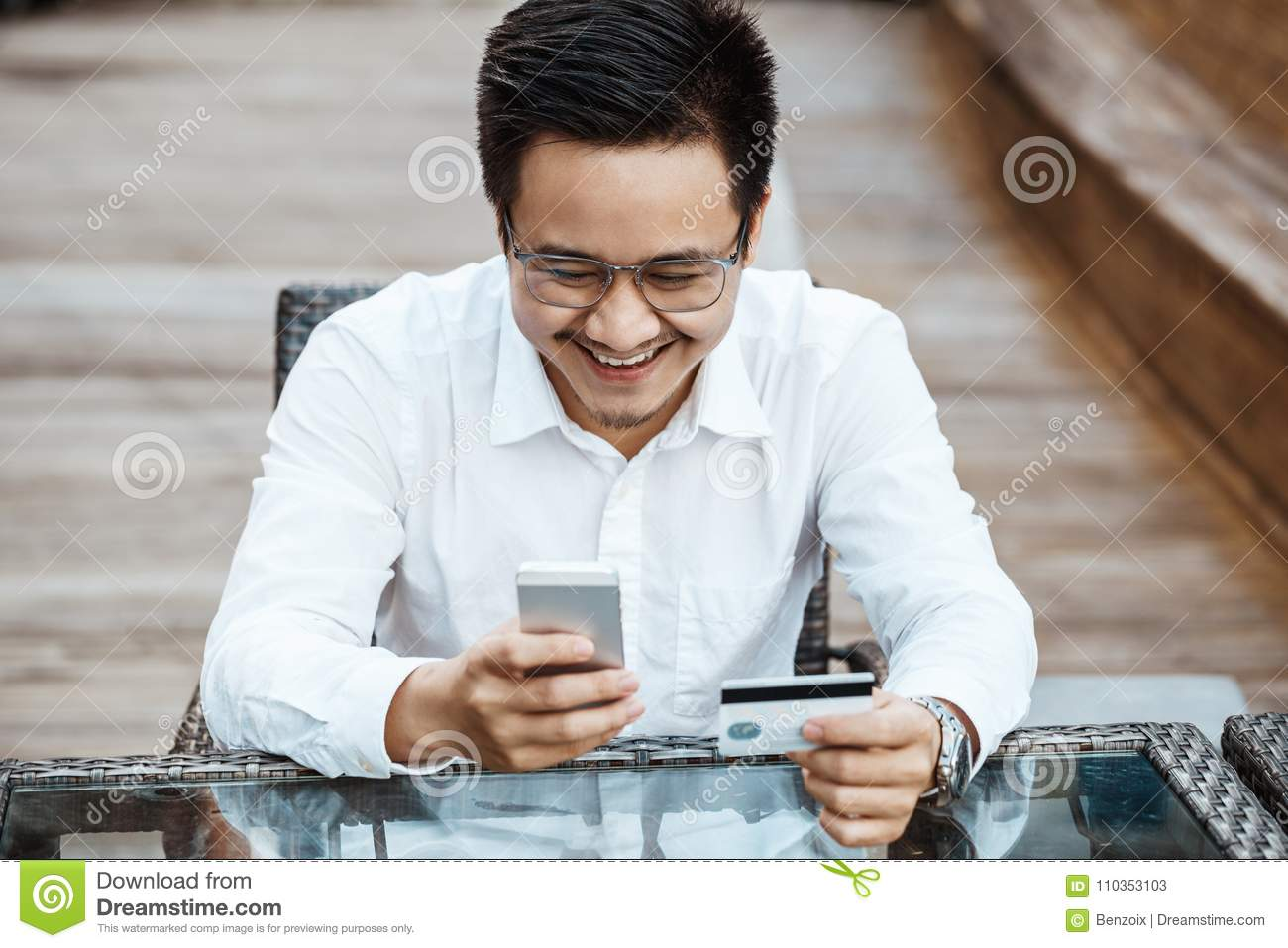 f35189a3fa7 Young Handsome man enjoy shopping online on mobile phone with credit card