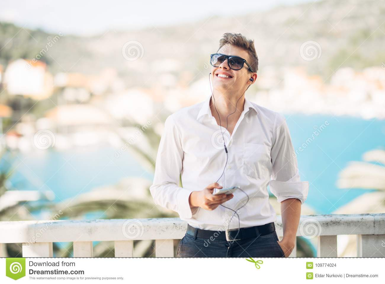 Young handsome man enjoying stay at luxury resort hotel with panoramic view on the sea