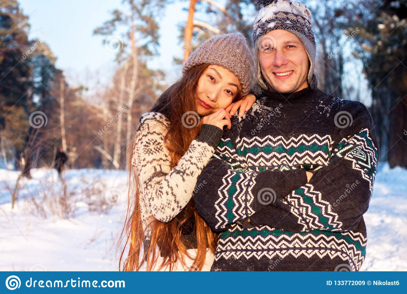 A young handsome man of European appearance and a young Asian girl in a park on the nature in winter