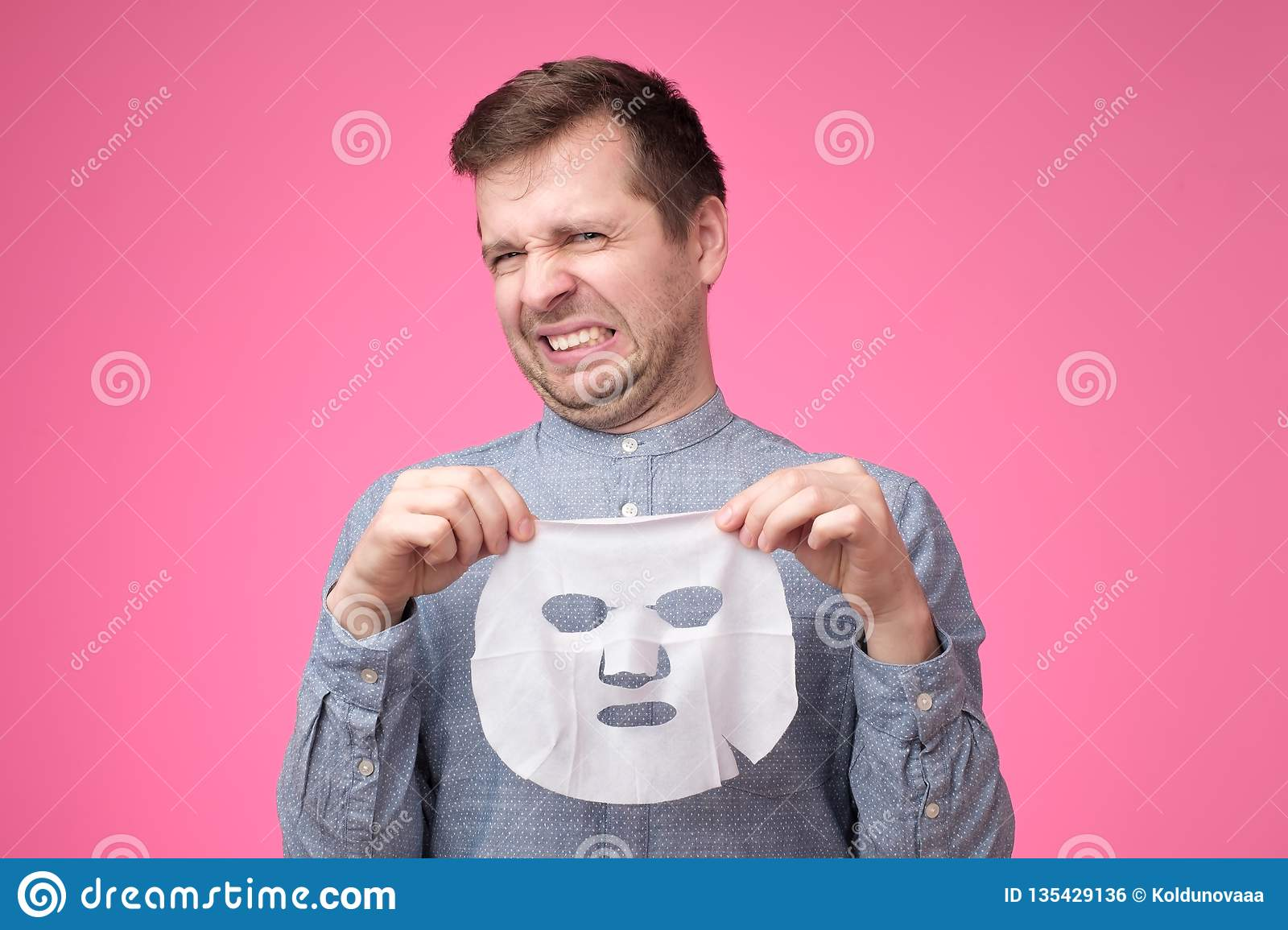Young handsome man holding cosmetic mask and looking puzzled standing on pink background.