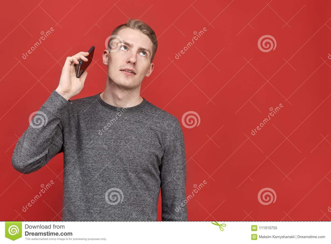 Young handsome man looking up from annoying boring conversation on phone. businessman tired of constant long calls from clients.