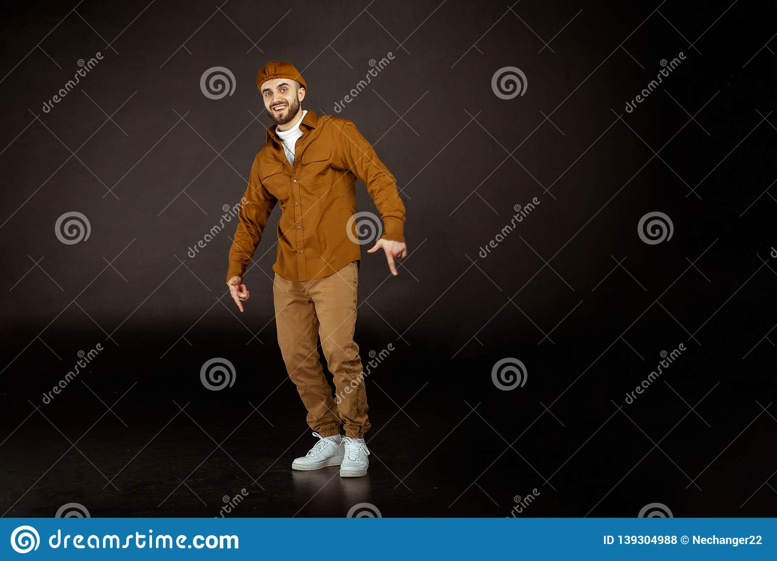 Young handsome man possing and modeling over grey isolated background,  looking at the camera, white shoes, studio photo