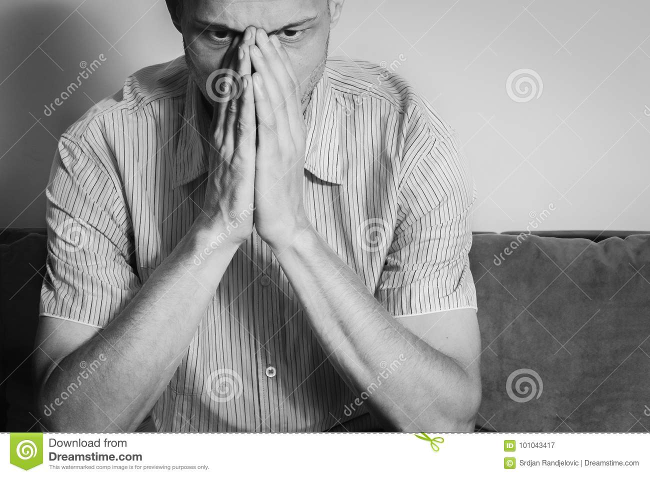 Young handsome man in the shirt cover his face with his hands feeling depressed and miserable while he thinking about life.