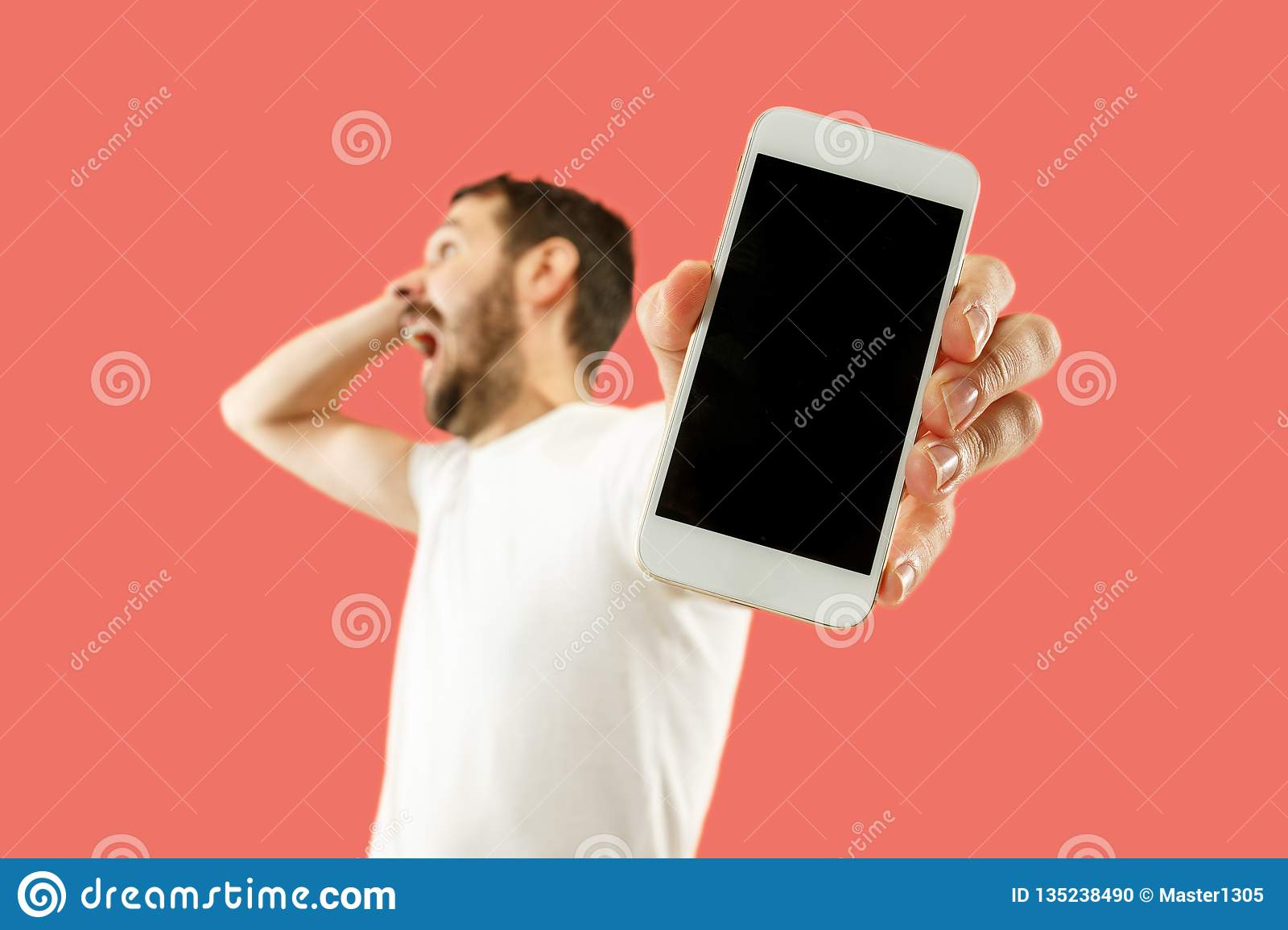 Young handsome man showing smartphone screen isolated on coral background in shock with a surprise face