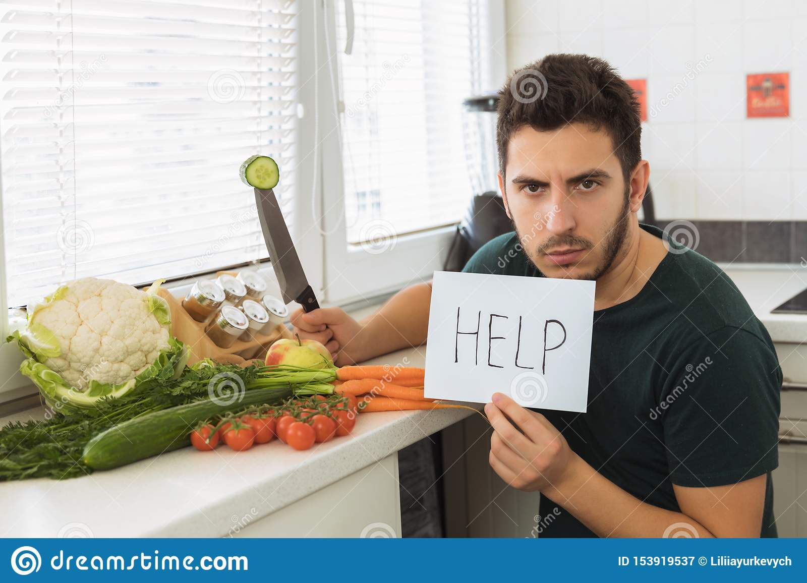 A young handsome man sits in the kitchen with an angry face and asks for help.
