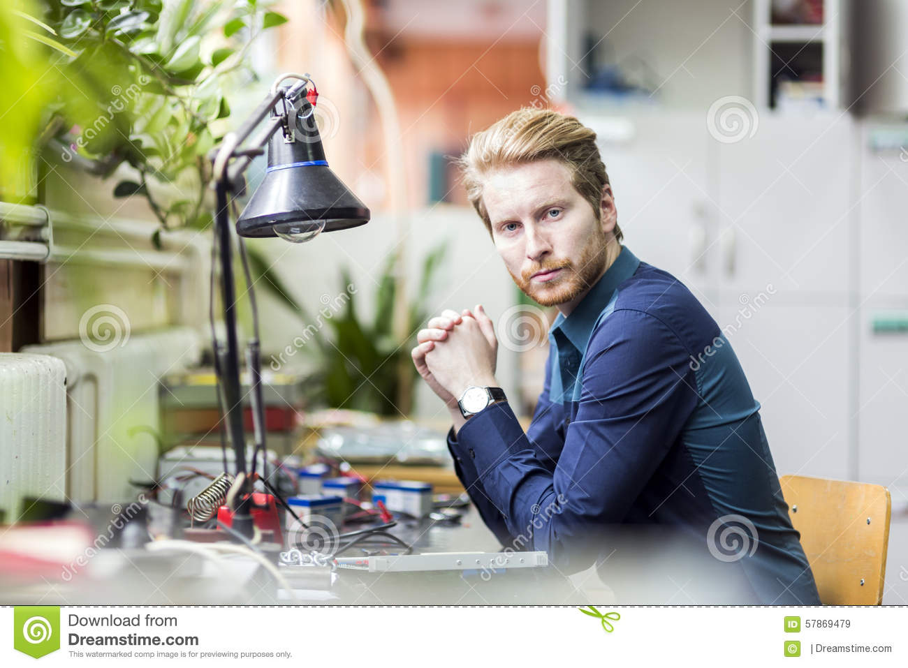 Young handsome man thinking how to solder the circuit board