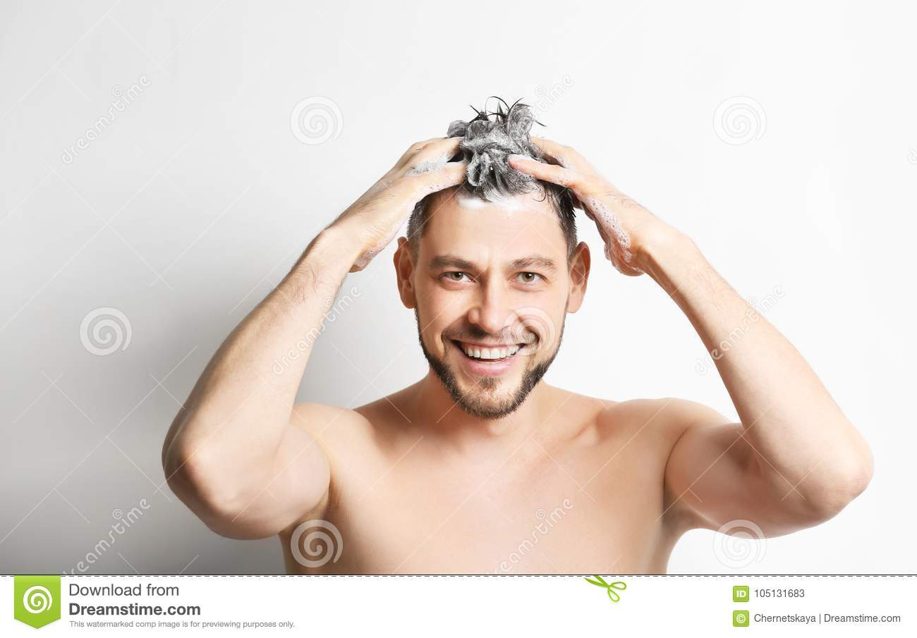 Young handsome man washing hair