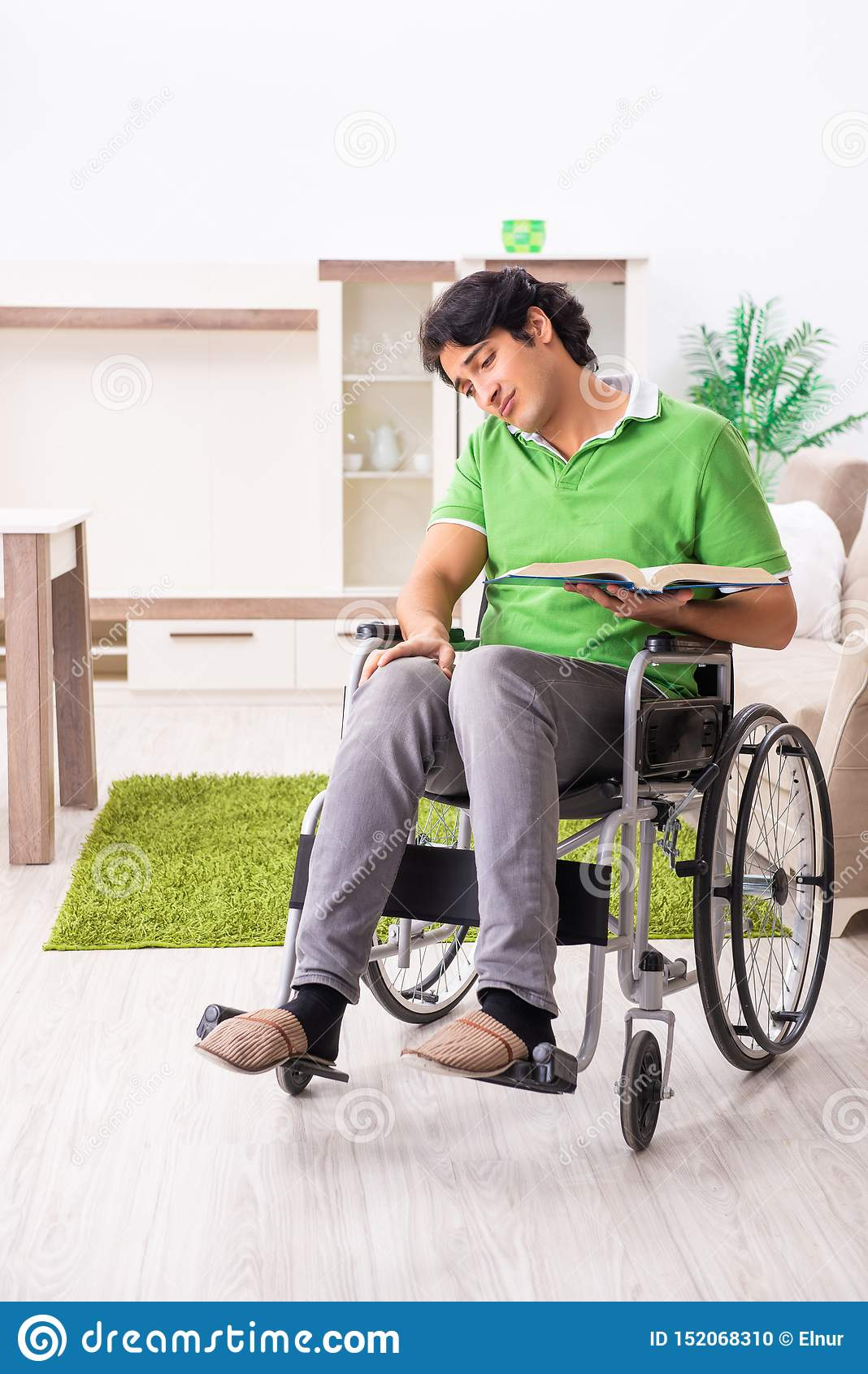 Young handsome man in wheelchair at home