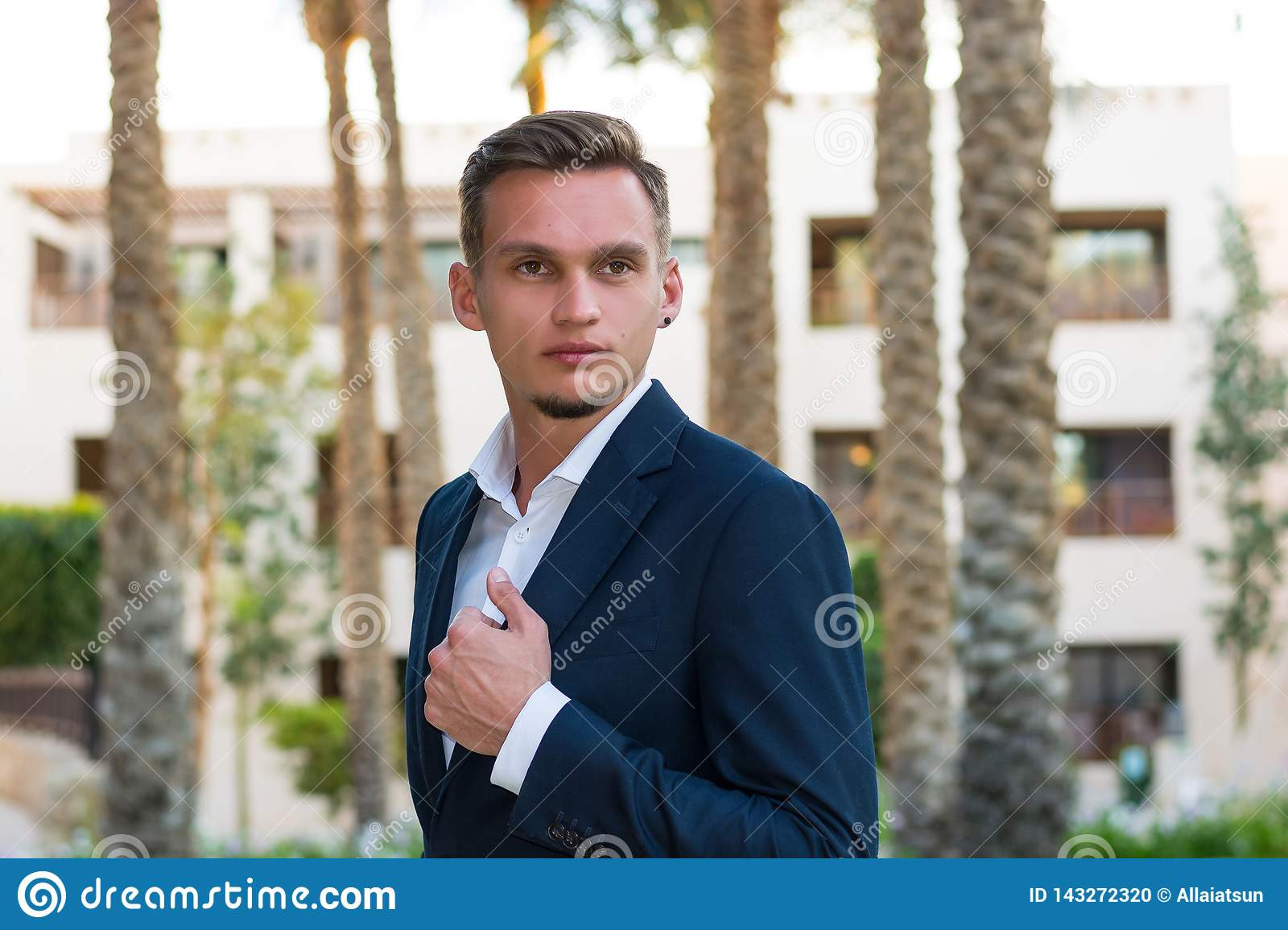 Young handsome man in a white shirt, white trousers and suit stands near the palm tree