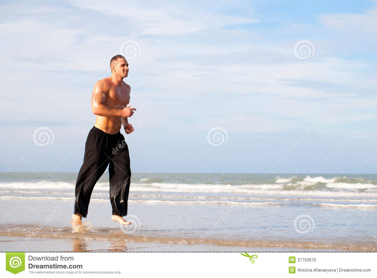 Young handsome muscular man running on the beach.
