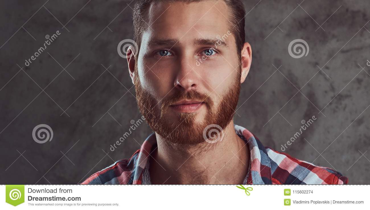 Young handsome redhead model man in a flannel shirt on a gray background.