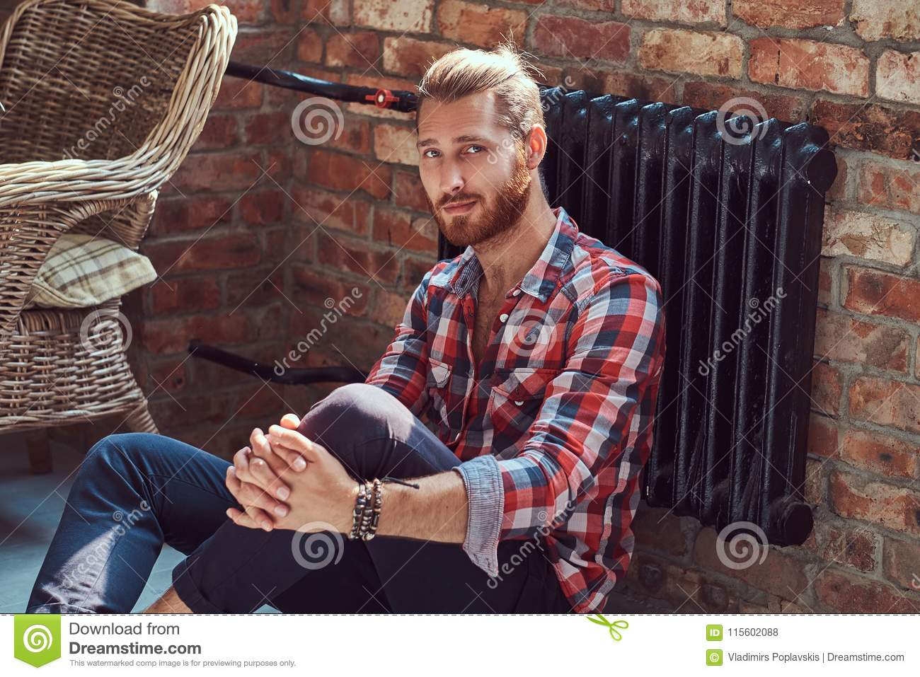 Young handsome redhead model man sits on a floor in the room with a loft interior.