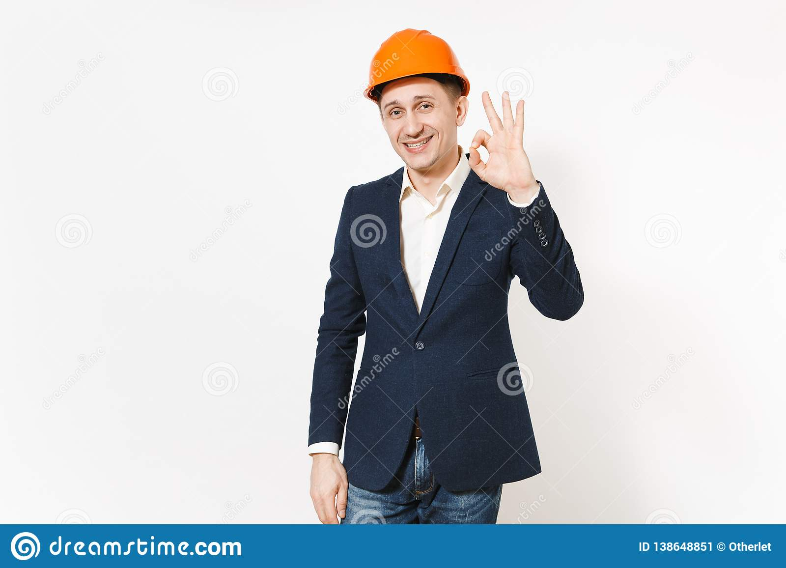 Young handsome smiling businessman in dark suit, protective construction orange helmet showing OK gesture isolated on