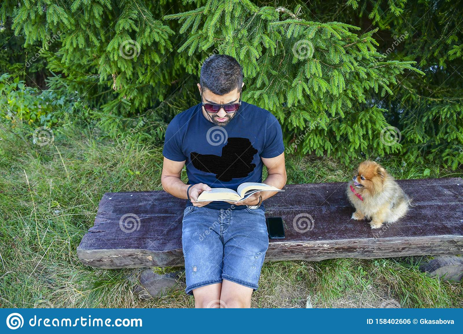 Young handsome smiling man reading outdoor with a dog
