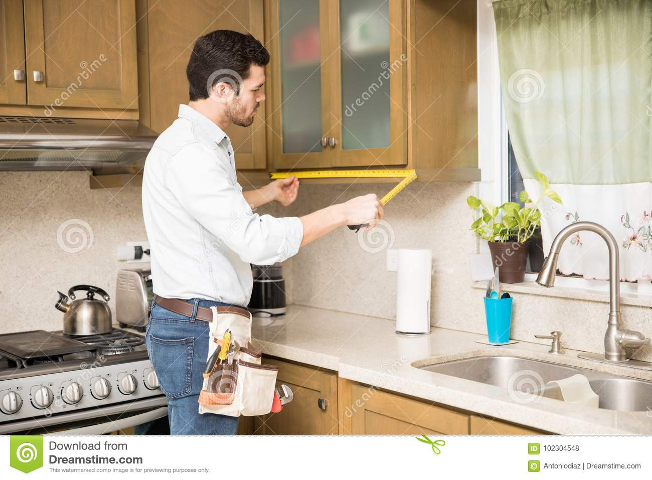 Handyman Measuring A Kitchen Cabinet Stock Photo - Image of kitchen ...