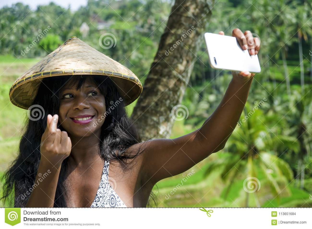 Young attractive happy afro american black woman tourist taking selfie portrait photo with mobile phone camera