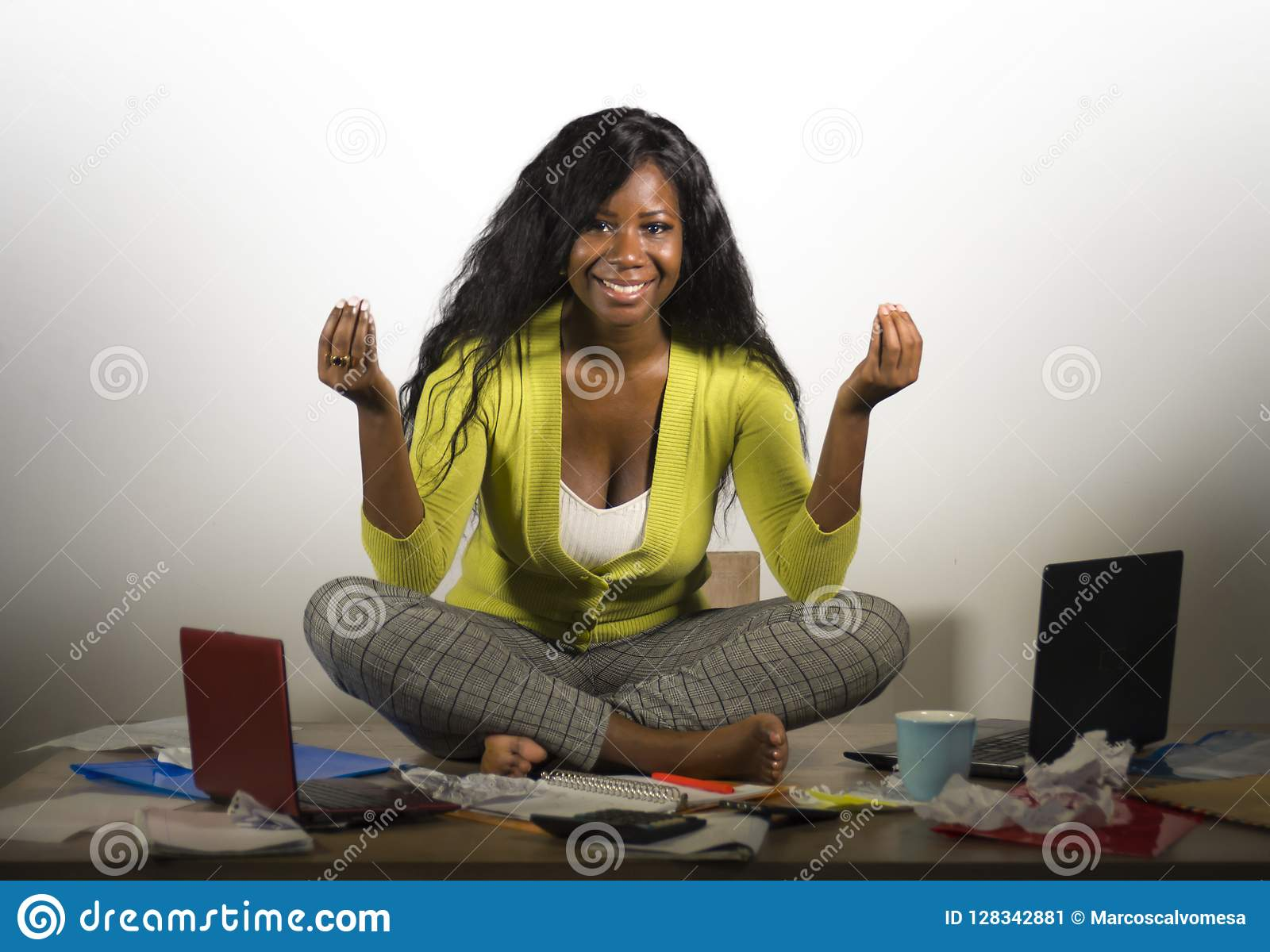 Young happy and attractive African American business woman doing yoga sitting at office messy desk full of paperwork smiling relax