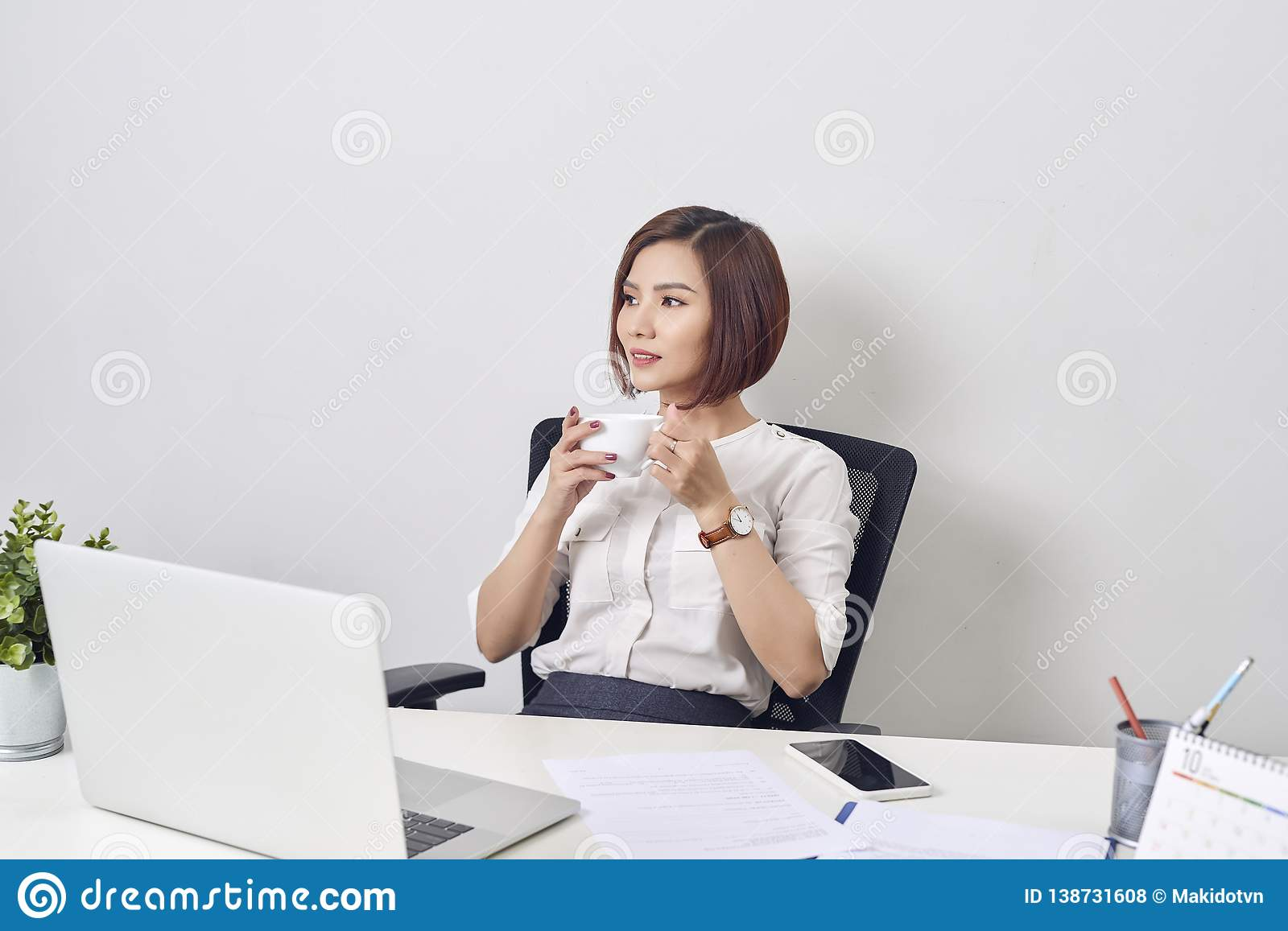 Young happy and attractive asian business woman working at office computer desk smiling drinking cup of coffee relaxed and