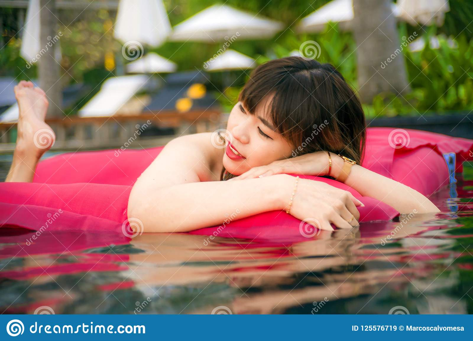 Young happy and attractive Asian Chinese woman enjoying at holidays resort swimming pool having fun in airbed smiling cheerful in