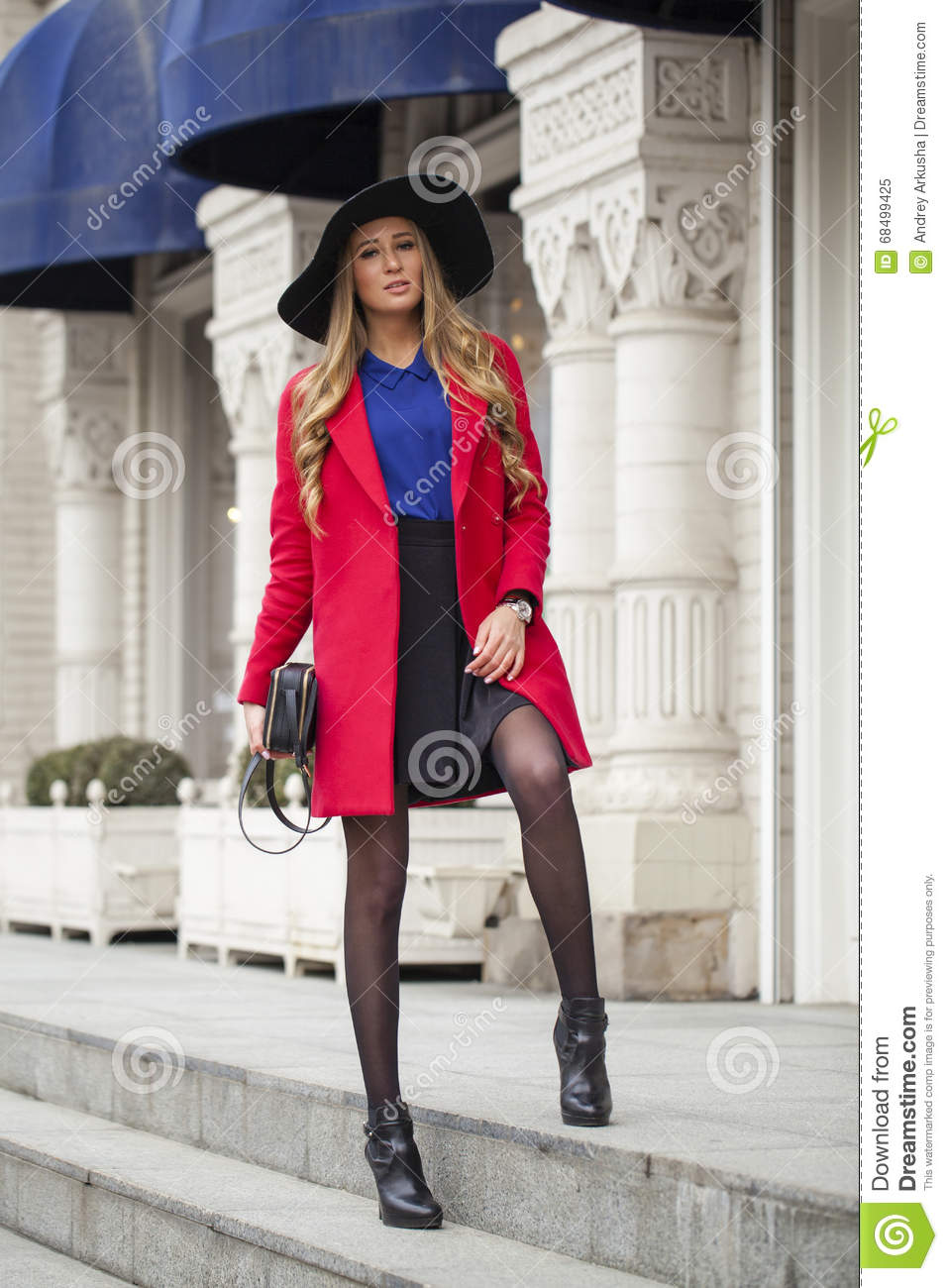 Young Happy Blonde Woman In Red Coat Walks On Spring Street Stock