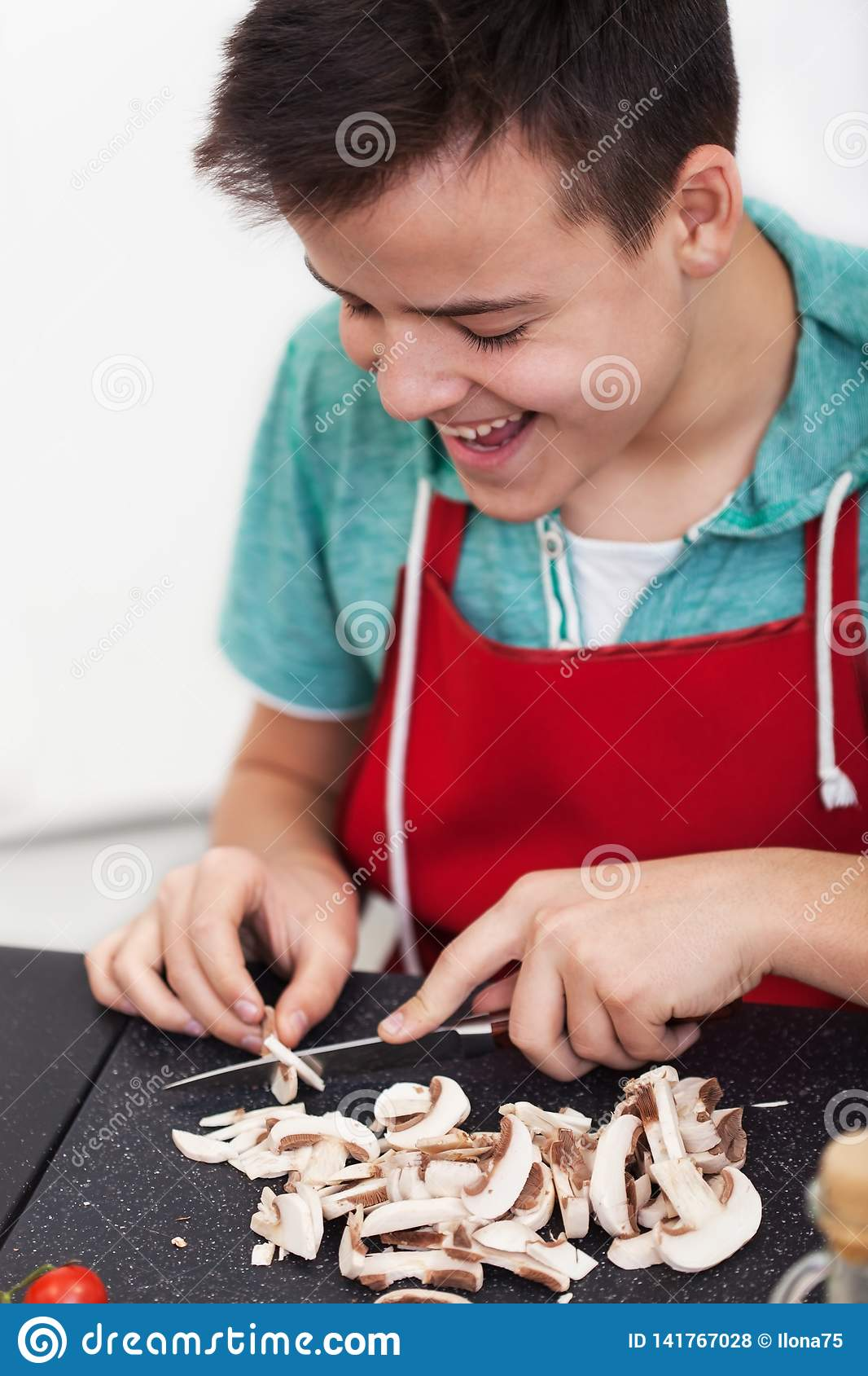 Young happy boy preparing a dish in the kitchen - slice mushrooms on cutting board