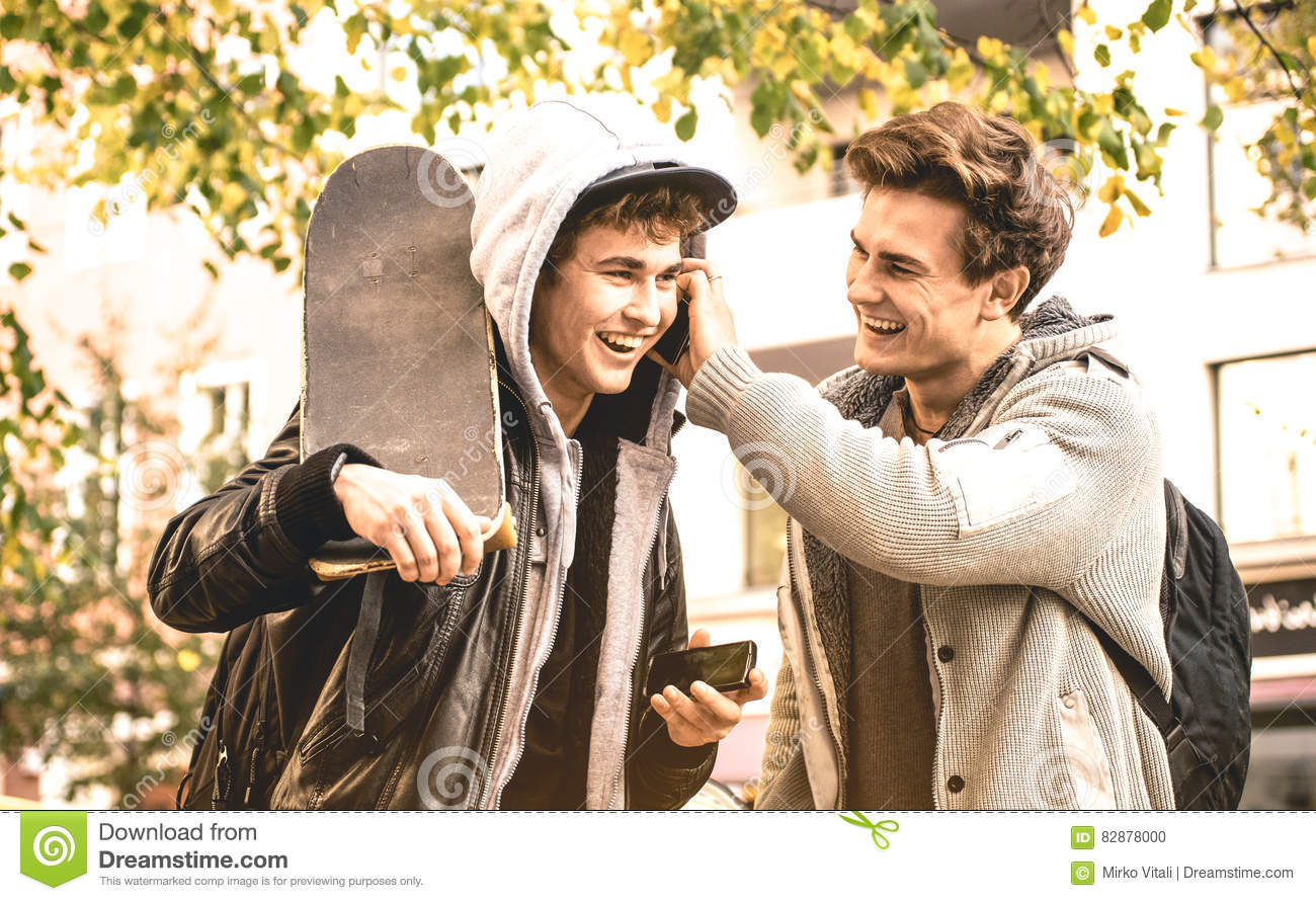 Young happy brothers having fun using mobile smart phones