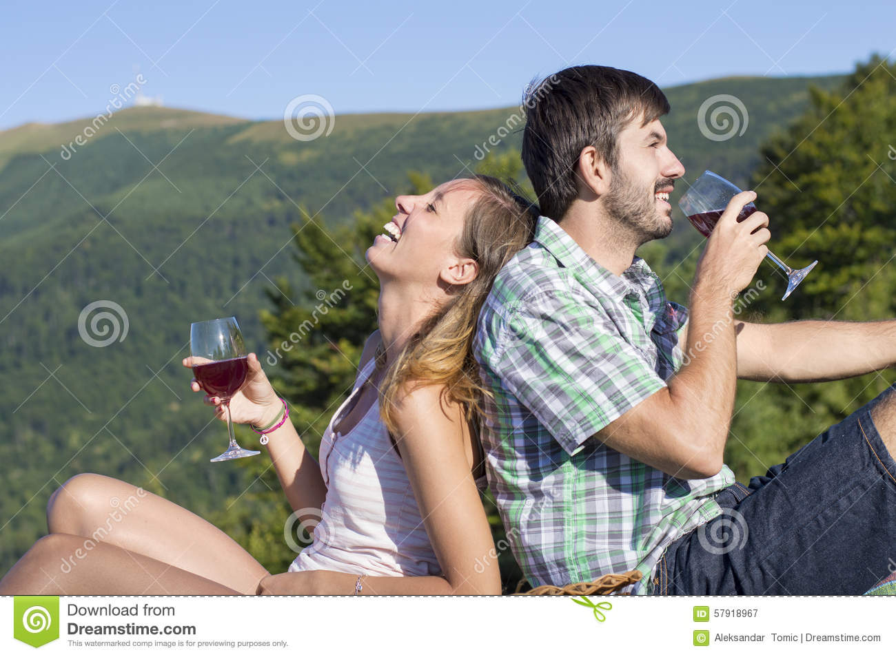 Young happy couple drinking wine on a hiking trip at the viewpoi