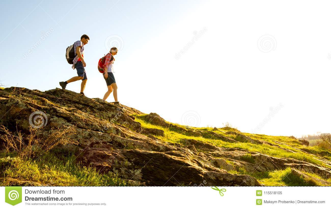 Young Happy Couple Hiking with Backpacks on the Beautiful Rocky Trail at Sunny Evening. Family Travel and Adventure.