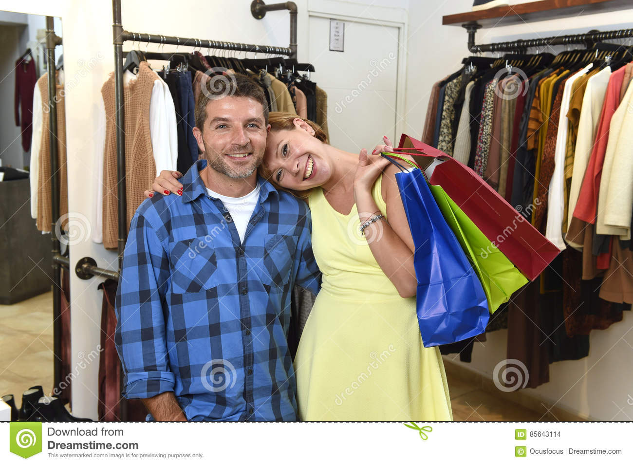 581104660e Young happy couple shopping together clothes at fashion shop smiling  satisfied in love gift