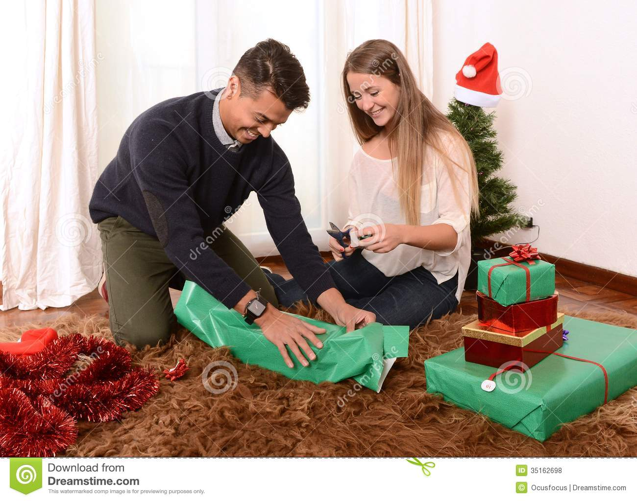 Young Happy Couple Wrapping Christmas Presents Royalty