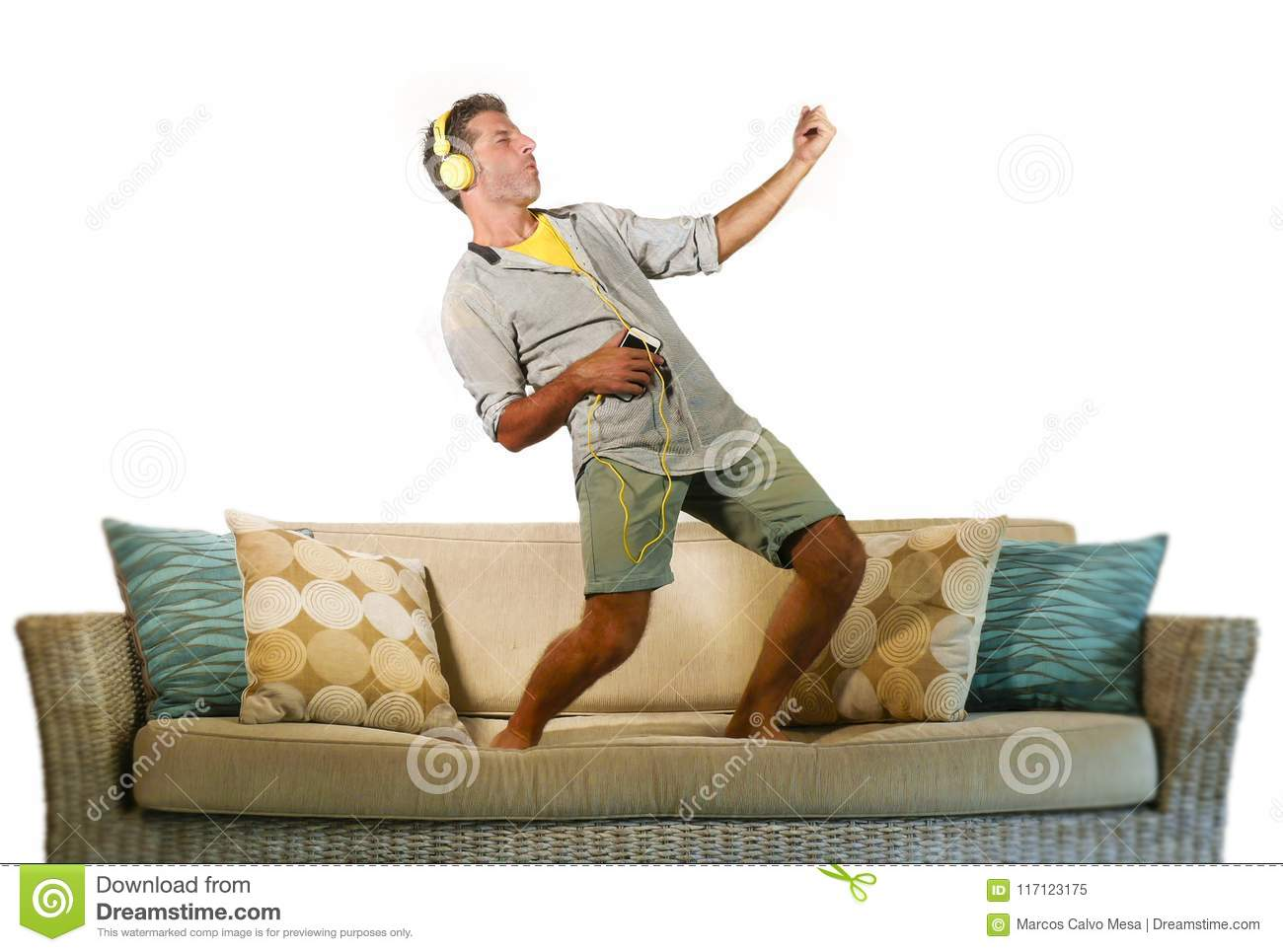 Young happy and excited man jumping on sofa couch listening to music with mobile phone and headphones playing air guitar crazy hav
