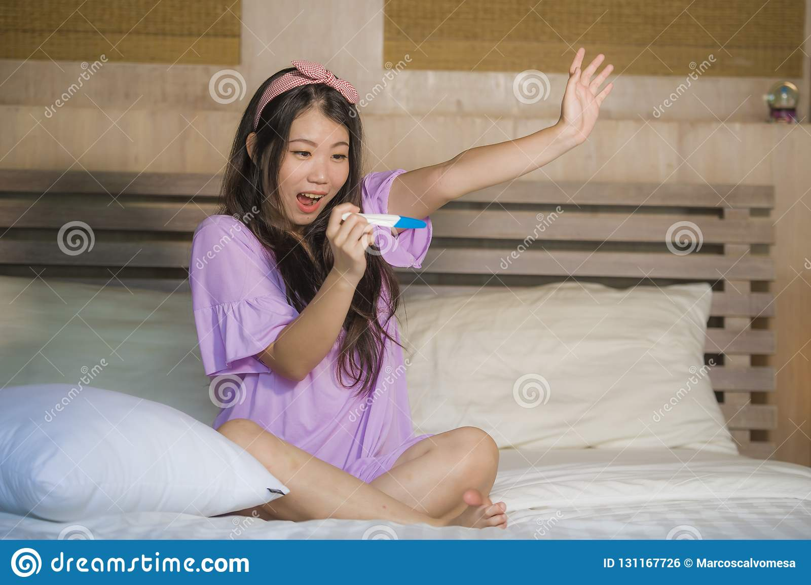 Young happy excited pregnant Asian Korean woman at home holding predictor and checking positive result on pregnancy test feeling b