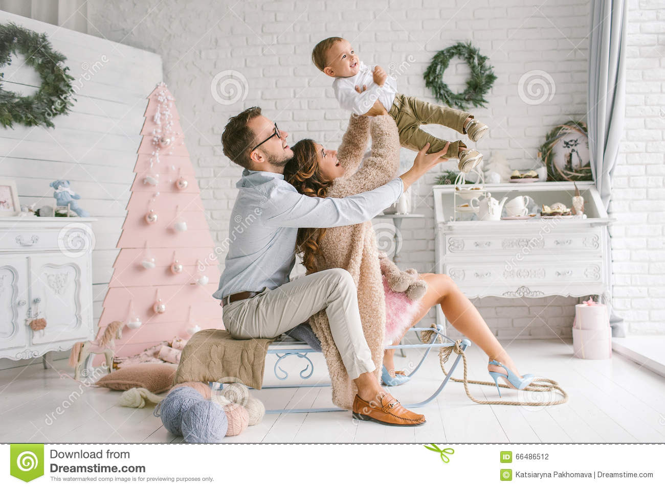 Young Happy Family Holding Baby In Christmas Decor Studio Stock ...