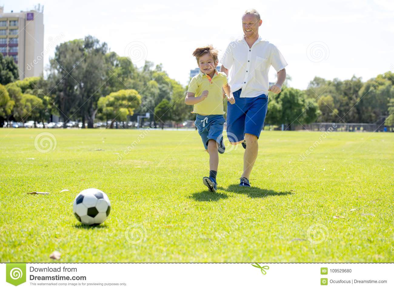 Young happy father and excited little 7 or 8 years old son playing together soccer football on city park garden running on grass k