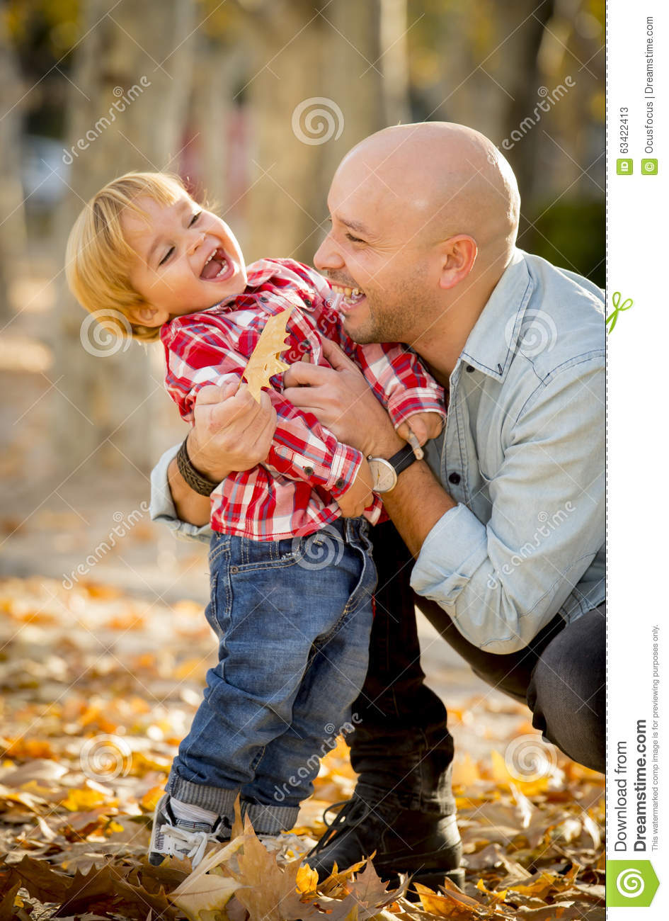 Young happy father playing with little cute son with tree leaves