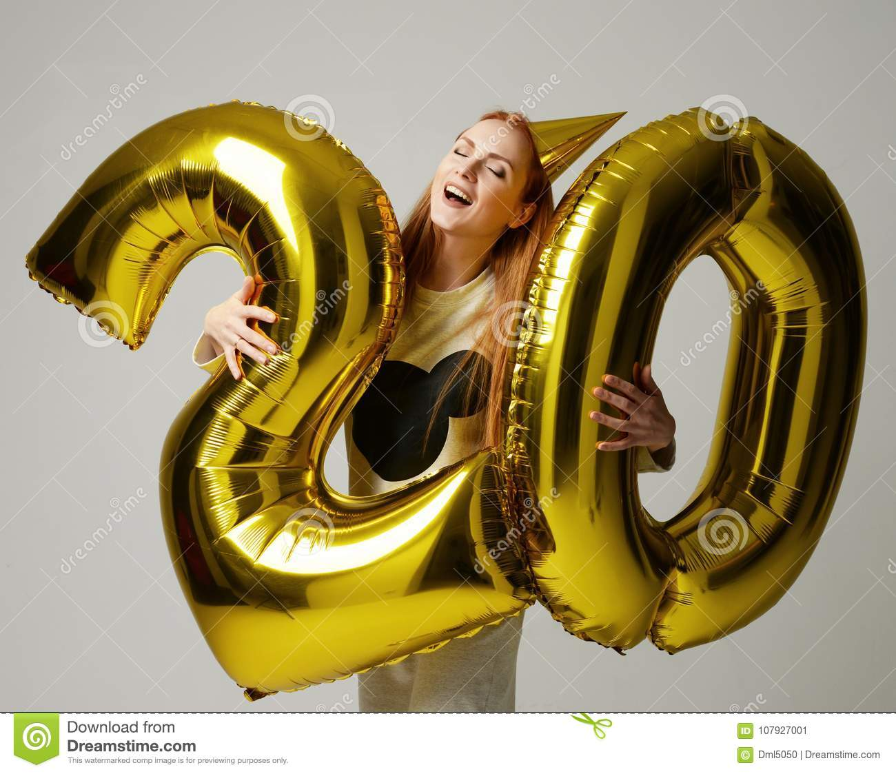 Young happy girl with huge gold digit twenty balloons as a present for birthday