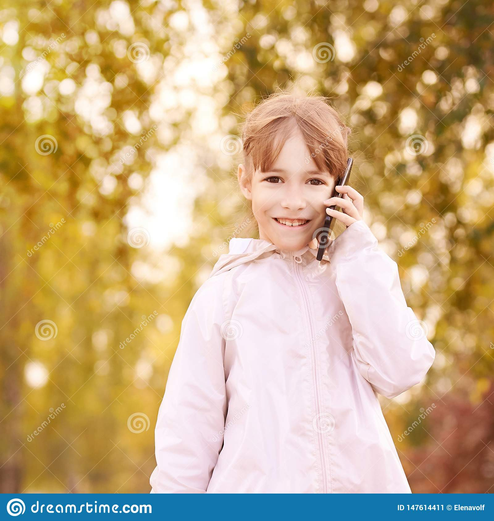Young happy girl talks cellphone. Phone roaming. People with smartphone. Autumn background