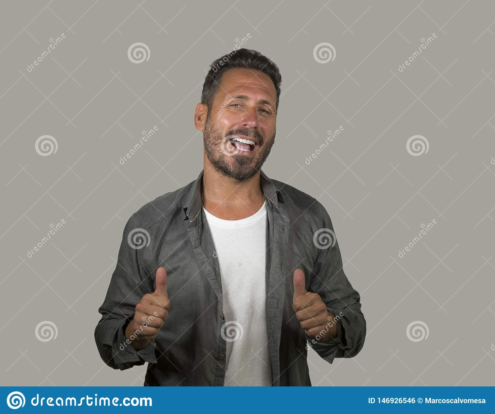 Young happy and handsome 40s man with blue eyes and beard  in casual shirt posing in cool attitude smiling cheerful and confident