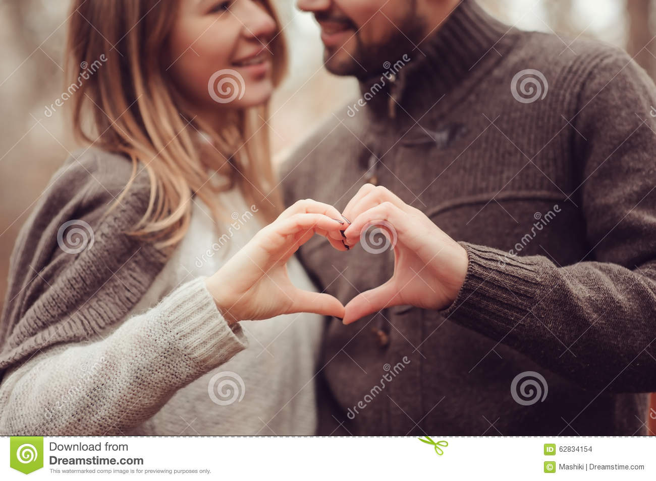 Young happy loving couple showing heart for valentine day on cozy outdoor walk in forest