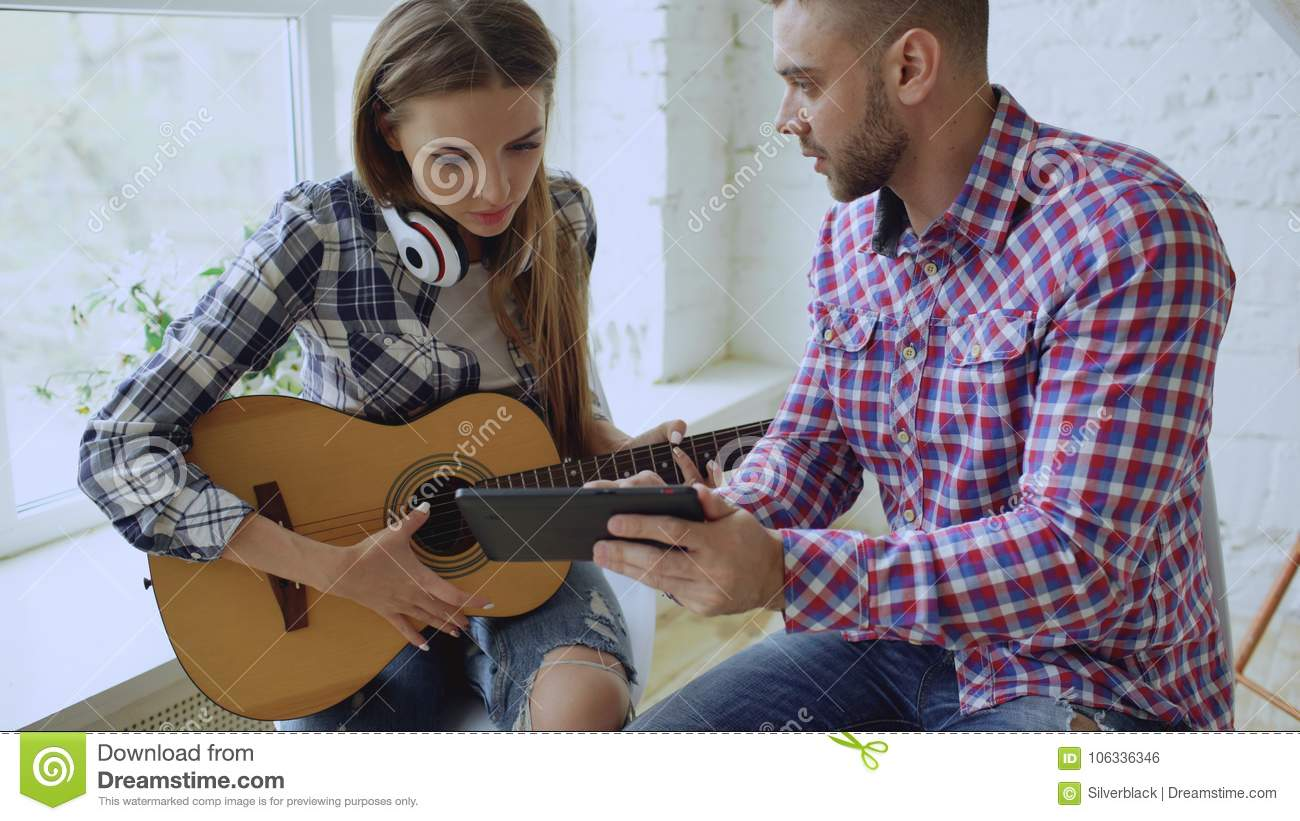 Young happy and loving couple study to play acoustic guitar using tablet computer and having fun while sitting at the