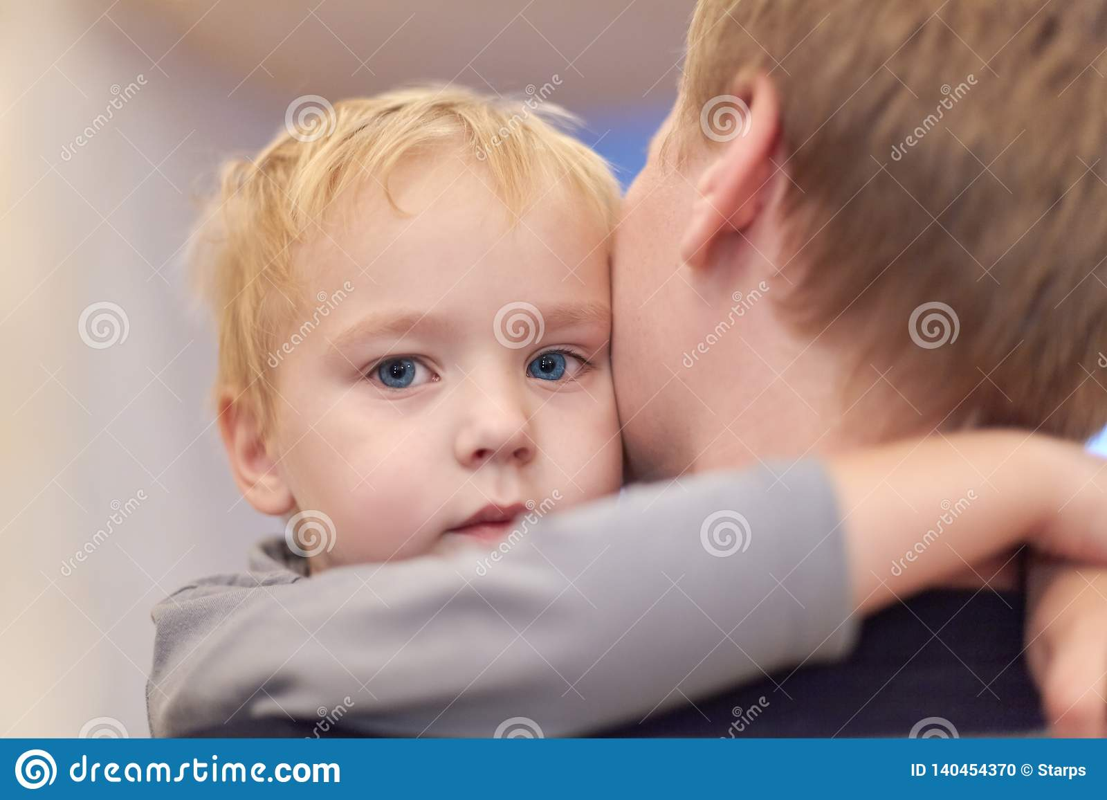 Young happy man holding his cute son. Baby boy embraces the male neck. Serious little kid with blue eyes napping in parent arms. S