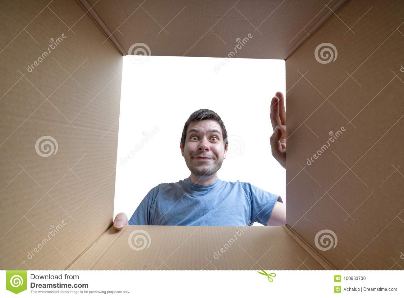 Young happy man is opening gift and looking inside cardboard box
