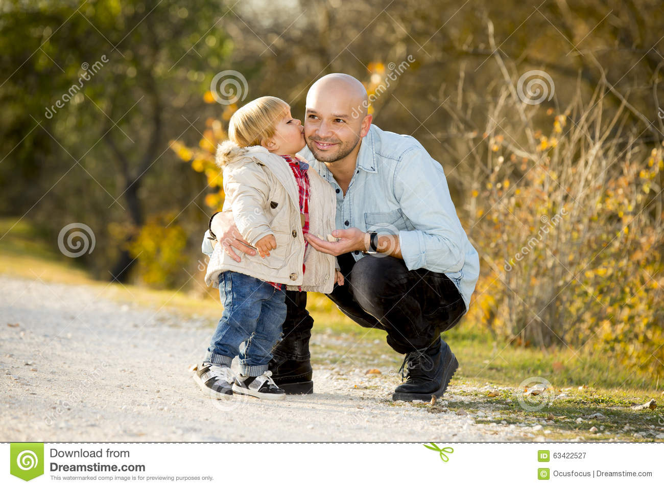 Young happy man playing with excited little cute son the child kissing his father