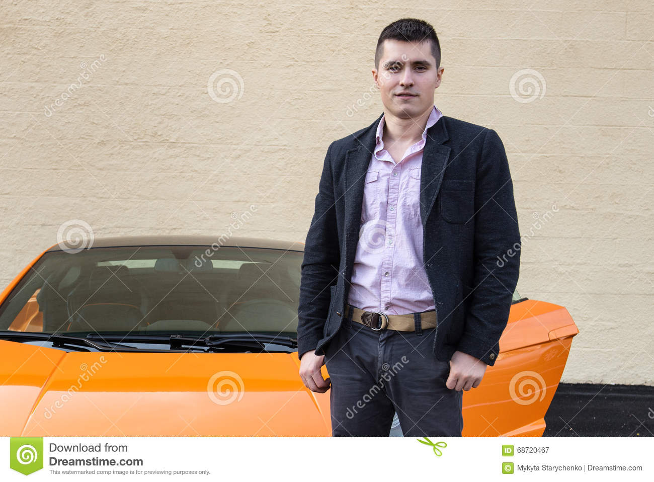 Young happy man standing near luxury sport car