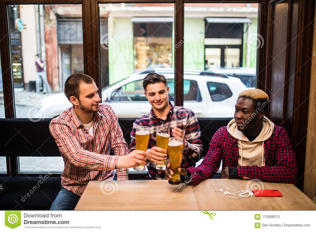 Young happy multiracial men friends drinking beer and talking in pub