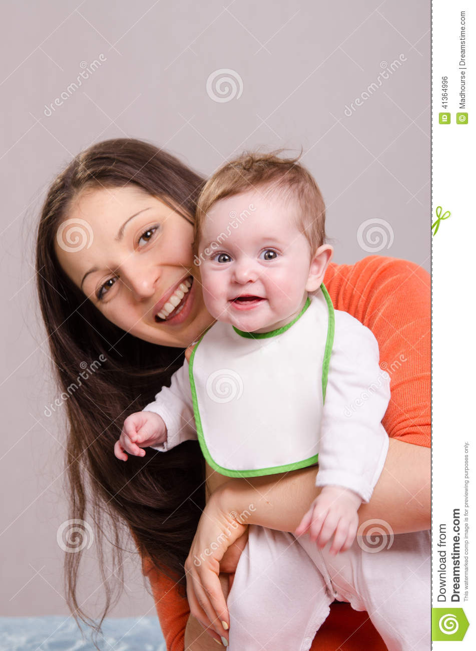 Young happy mother hugging baby girl in bib
