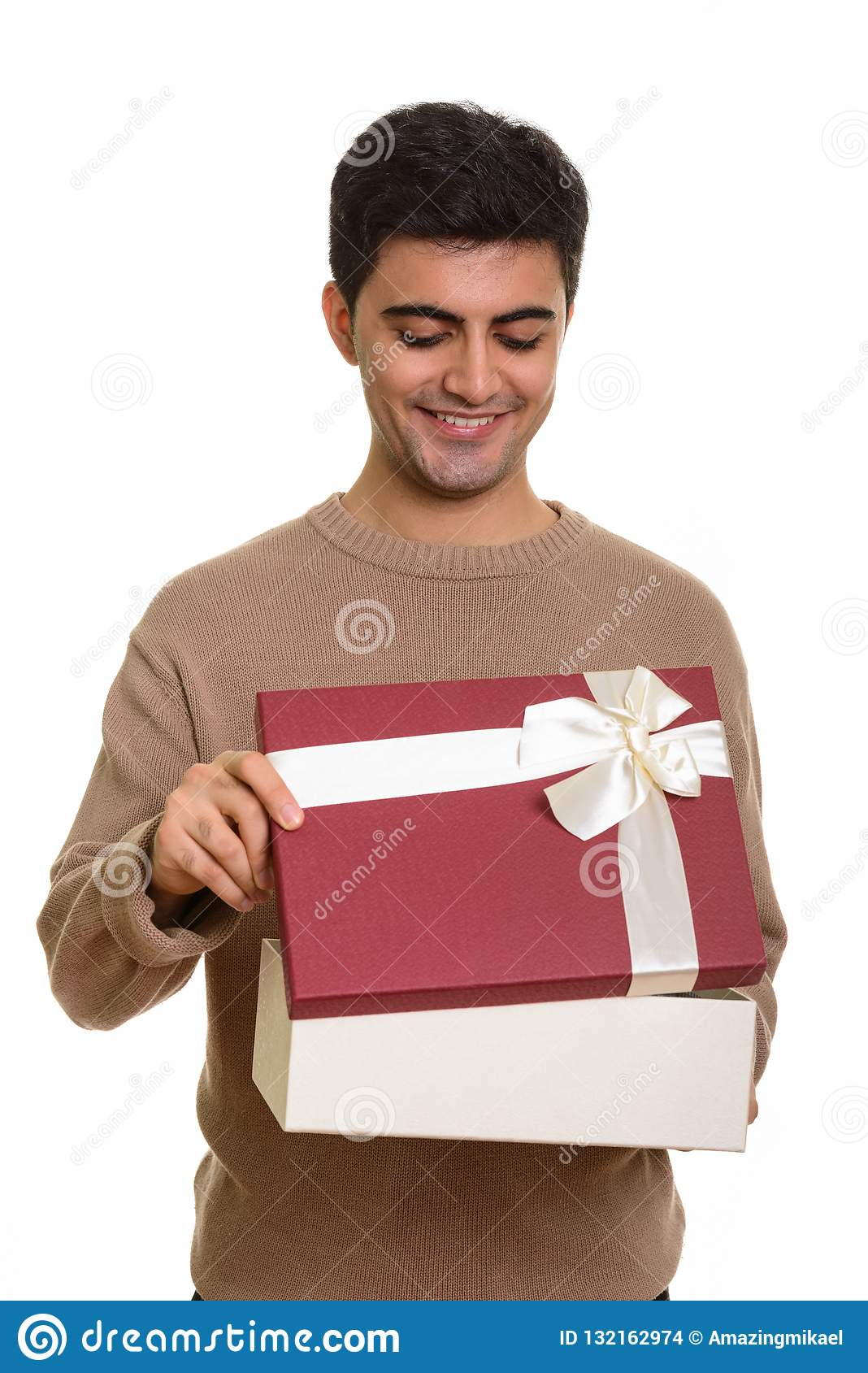 Young happy Persian man opening gift box ready for Valentine`s d
